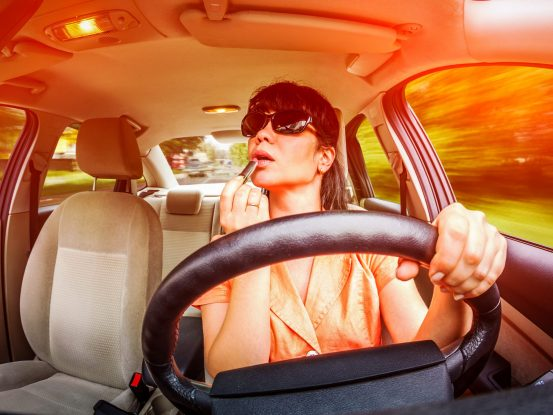 Image of a woman putting lipstick on her lips while at the wheel of a car