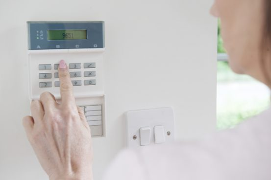 Image of woman pushing the buttons on a home security system.