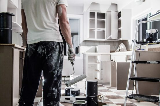 Image of man from behind standing in front of a freshly painted white kitchen with paint roller in hand