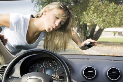 Image of woman in white tshirt kissing the windshield of her newly purchased vehicle.
