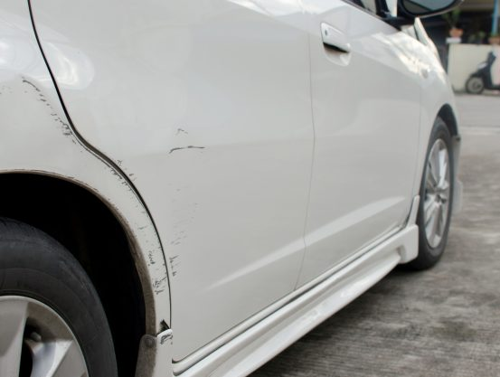Image of a white car with scratches along the right side of the vehicle